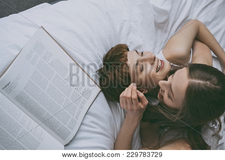 High Angle View Of Young Lesbian Couple Cuddling In Bed