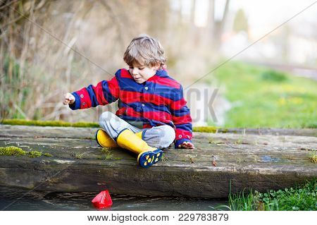Happy Little Kid Boy In Yellow Rain Boots Playing With Paper Ship Boat By Huge Puddle On Spring Or A
