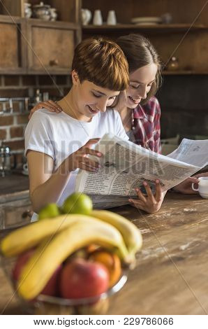Young Lesbian Couple Reading Newspaper Together On Kitchen