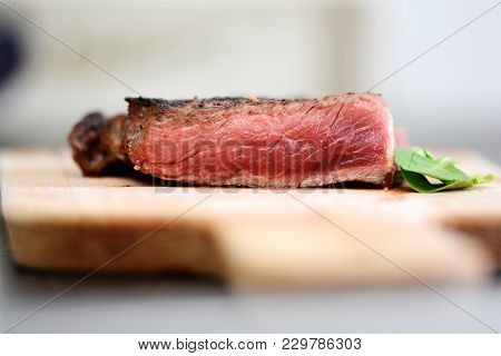 Sliced Medium Rare Grilled Steak On Wooden Cutting Board With Green Leafs And Spices