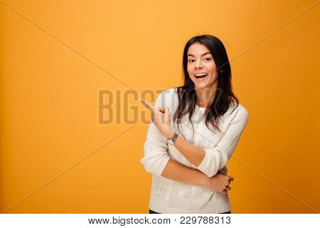 Portrait of a happy young woman pointing finger away at copy space isolated over yellow background