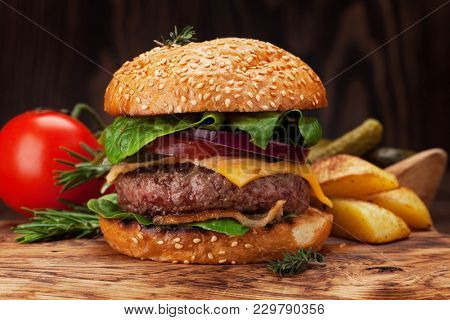 Tasty grilled home made burger with beef, tomato, cheese, cucumber and lettuce