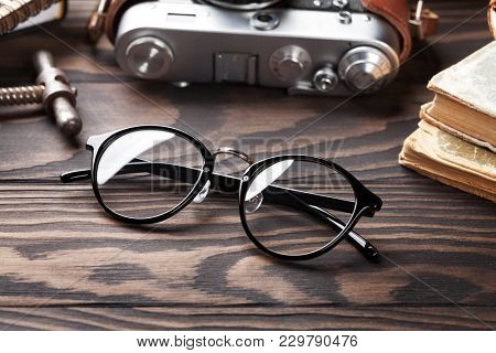 Retro table with vintage items. Old books, glasses, camera and wine corkscrew