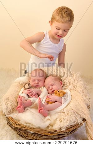 Toddler boy posing with his newborn identical twin sisters