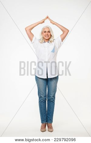 Full length portrait of a happy mature woman standing and holding two hands above her head isolated over white background