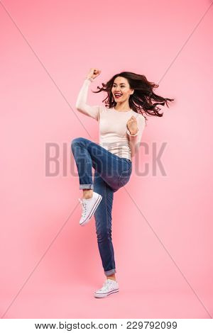 Full length photo of joyous woman with long brown hair expressing happiness and luck with clenching fists isolated over pink background
