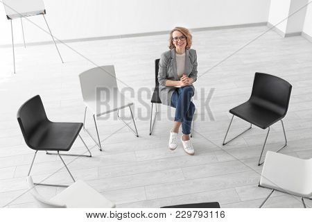 Female psychologist in room with chairs prepared for group psychotherapy session