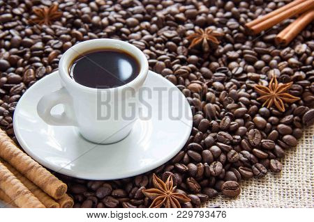 Roasted Roasted Coffee Beans With A Cup On A Saucer With An Espresso Drink With Cinnamon And Aniseco