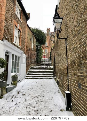 HAMPSTEAD, LONDON - MARCH 1, 2018: Footpath and steps covered in snow during Storm Emma, also know as the 'Beast from the East' weather front, in quaint and historic Hampstead, North London, UK.
