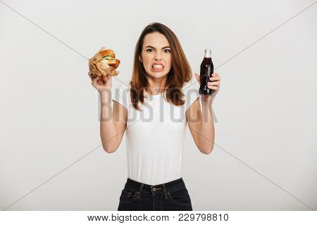 Picture of displeased young woman standing isolated over grey wall background holding burger and soda.
