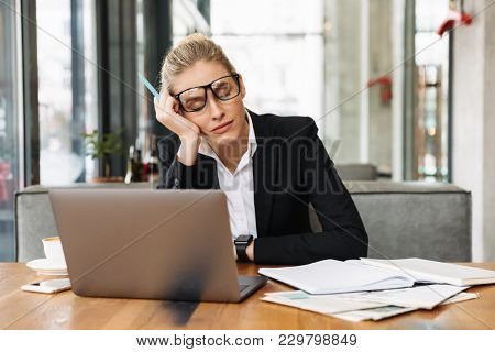 Tired blonde business woman sitting by the table in cafe with laptop computer while closing eyes and reclines on hand