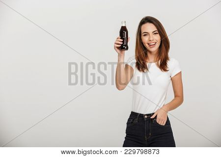 Image of cheerful young woman standing isolated over grey wall background holding bottle with soda.