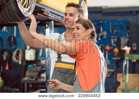 Two dedicated auto mechanics smiling happy, while checking the modified wheels of a tuned car after working together in a modern automobile repair shop with tuning service