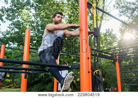 Low-angle view of a determined handsome man passionate about fitness doing extreme single-leg squats on the equipment of a modern calisthenics park