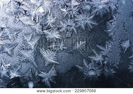 Ornaments On A Frozen Window On A Black Background In Blue. Frozen Water On The Window Creates Silve