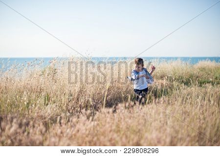 Free Little Boy Running Across Field Of Dried Grass On Sea Background