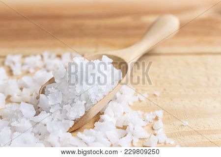 Sea Salt In A Wooden Spoon On The Table. Sea Salt Is Used For Seasoning, Preserving Food And Making