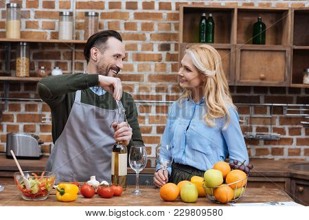 Smiling Husband Opening Wine Bottle With Corkscrew And Looking At Wife