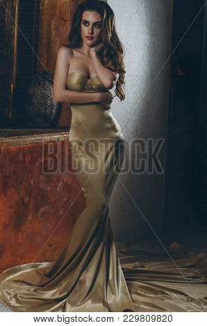 Attractive, Sexy, Sensual Brown-haired In A Golden Evening Dress Posing In The Interior. Fashion Pho