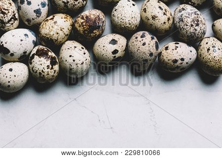 Spotted quail eggs on a white marble background. Easter traditions. Copyspace.