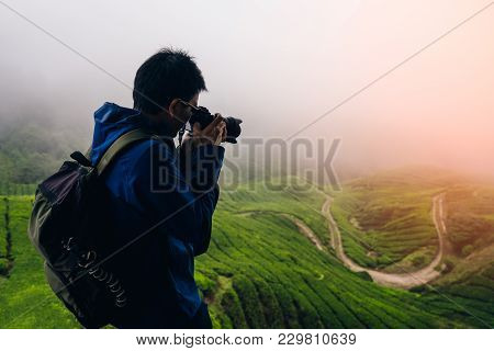 Young Asian Backpacker Traveling Into Tea Fields With Mist. Young Man Traveler Take A Photo Of Mount