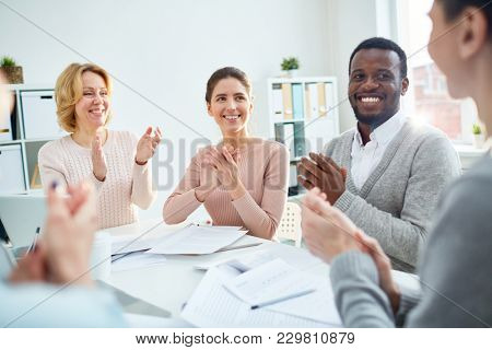 Smiling associates applauding to their colleague after report at working briefing