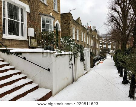 HAMPSTEAD, LONDON - MARCH 1, 2018: Snow covered footpath in quaint streets of Hampstead during Storm Emma, also named the 'Beast from the East', in North London, UK.