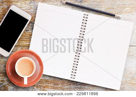 Office Desk Table-blank Paper Notebook,smartphone With Pencil And Cup Of Coffee On Wooden Table.view