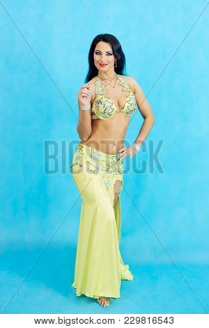 Charming Dancer Performs Oriental Belly Dance On A Blue Background.