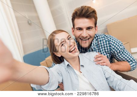 A Young Couple Makes Selfie While Moving To A New Apartment. Moving Newlyweds To New Housing
