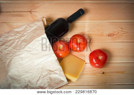 Fresh Tomatoes, Bottle Of Red Wine And Parmesan Cheese In Paper Bag