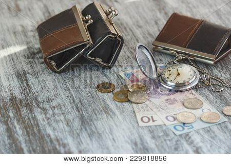 Polish Zloty With Little Wallets And Pocket Watch On The Wooden Background