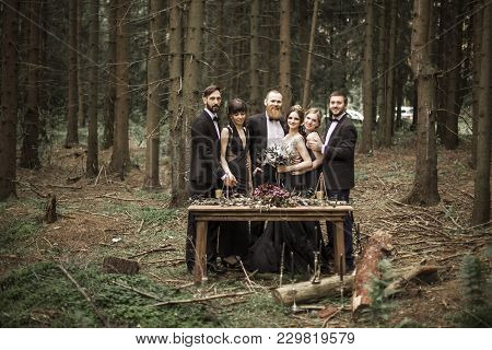 Portrait Of The Couple And The Witnesses Near The Picnic Table In The Woods