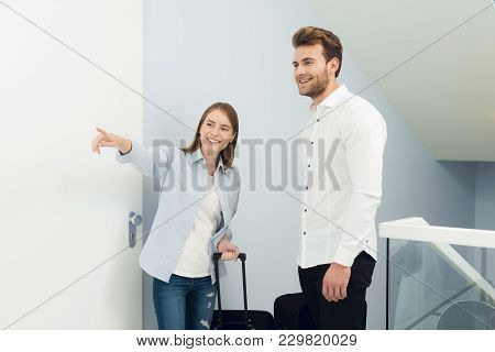 The Young Couple Moved To Their Own Apartment. They Stand With Suitcases In The Entrance. The Girl A