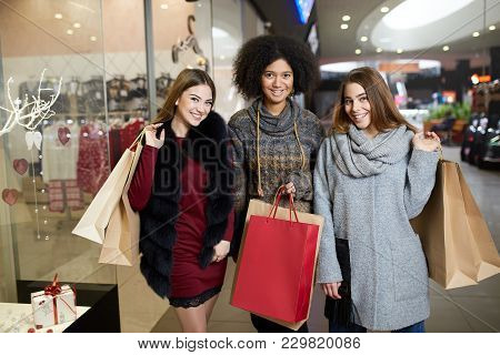 Happy Stylish Young Multiethnic Women With Shopping Bags Walking In Shopping Mall With Paper Eco Bag