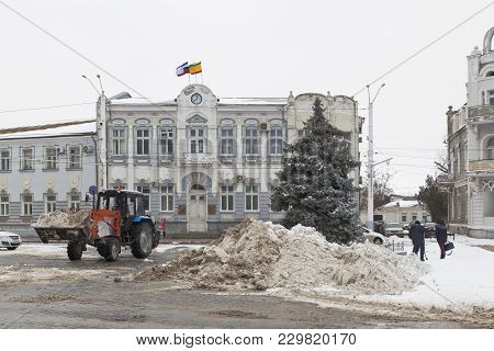 Evpatoria, Crimea, Russia - February 28, 2018: Snow-removal Work On The Background Of The Building O