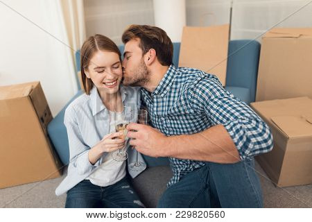 Young Couple Celebrating With Champagne Moving To New Apartment. Moving Newlyweds To New Housing.