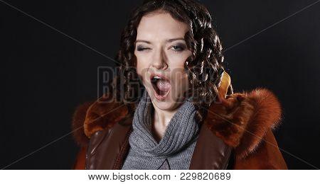 Girl In Fur Coat Yawns Of Boredom On Black Background