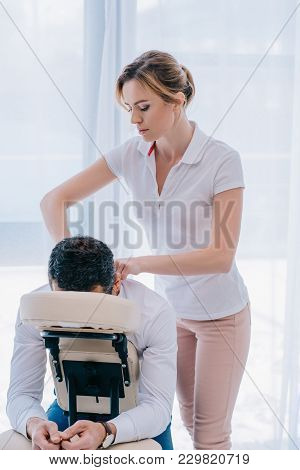 Attractive Masseuse Doing Shoulders Massage On Seat At Office