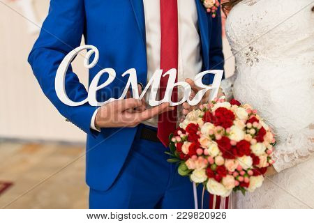 The Bride In White Dress And Groom In Blue Suit Holding Wooden Inscription