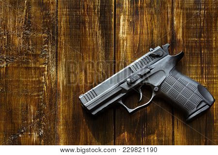 A black pistol with a plastic knurled grip is isolated on the background of a wooden table made of walnut. poster