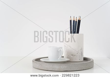 Coffee Cup And Pencils On Grey Concrete Tray. Front View