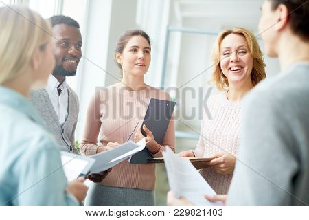 Group of financiers with papers having briefing where discussing documents or methods of working