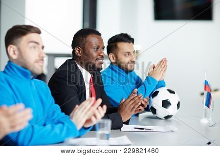Elegant football trainer and his players in sportswear clapping hands after speech at conference