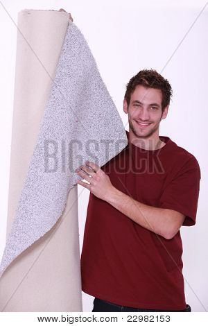 Young man standing with roll of carpet