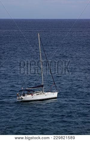 White Sailboat With A Descended Sail On A Sunny Day At Sea