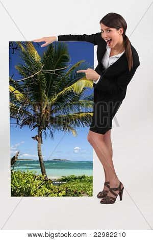 female travel agent showing poster of tropical beach