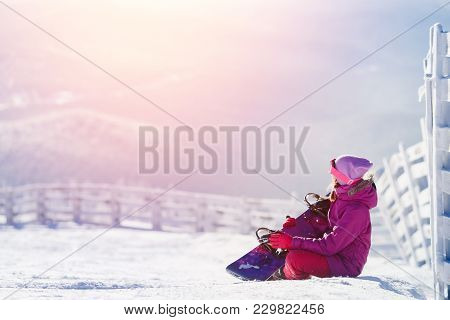 Snowboarding. Girl Is Sitting Hugging Snowboard Showing Love Of Sport, In Background Of Mountain In