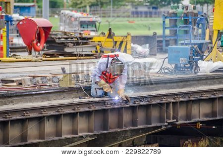Welder Making Maintenance Work On One Of The Lock Gates Of Panama Canal, Surrounded With Welding Fum