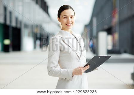 Young contemporary employee in formalwear holding financial document while working in airport